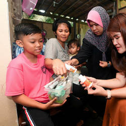 Member of Parliament, Wong Shir Yee (right) inspects the cancer medication used by 12-year-old Cyle Addel, at 27 Mile, Sandakan today. — Bernama