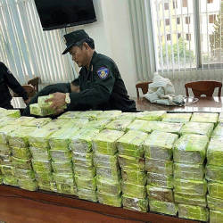 Vietnamese policemen arrange seized methamphetamine at a police station in Ho Chi Minh City. — AFP