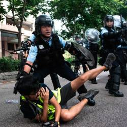 A photojournalist falls down during clashes between protesters and police at an anti parallel trading march in Sheung Shui district in Hong Kong on July 13, 2019. - AFP