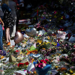 Floral tributes to those who were gunned down at the two mosques are seen against a wall bordering the Botanical Garden in Christchurch — AFP