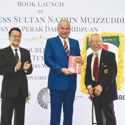 "Sultan Nazrin with the first copy of ""Trying Troubled Times Amid Trauma and Tumult"". With him are Lin (right) and Cheah (left)."