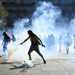 Protesters stand amid tear gas at the Place de la Republique during an anti-government demonstration called by the 'Yellow Vests' (gilets jaunes) movement, on April 20, 2019 in Paris. — AFP