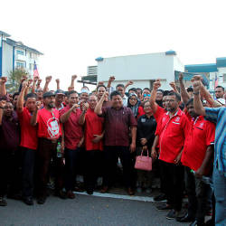 Johor Bersatu chief Mazlan Bujang, posts with his supporters after lodging a report at the Bandar Dato Onn police station, on Aug 24, 2019. — Bernama