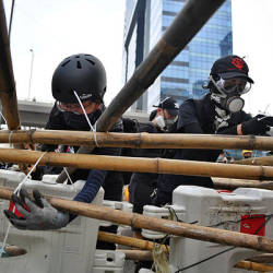 Protesters build barriers as they block a road in Hong Kong's Kowloon Bay on Aug 24. — AFP