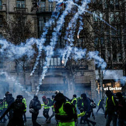 Protesters wearing yellow vests (gilets jaunes) stand amid smoke of tear gas during a demonstration against rising costs of living they blame on high taxes on the Champs-Elysees avenue in Paris, on Dec 15, 2018. — AFP