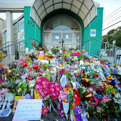 Flowers left by residents are seen at a memorial site for victims of the Christchurch mosque attacks at an Islamic Center in Kilbirnie, Wellington — AFP