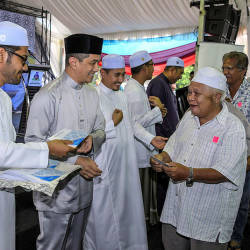 Economic Affairs Minister Datuk Seri Mohamed Azmin Ali (2nd L) hands out aid to senior citizens after the Iftar Perdana Council in the Gombak Setia constituency. — Bernama