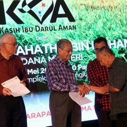 Prime Minister Tun Dr Mahathir Mohamad hands over donations to farmers during a ceremony at the Langkawi District Civil Defence Complex. - Bernama
