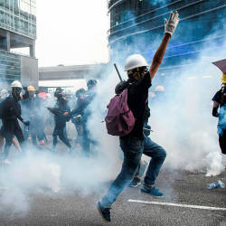 Protesters reacts as Police fire tear gas towards them in Kowloon Bay in Hong Kong on Aug 24, 2019. — AFP