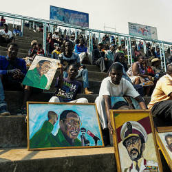 An artist sits among portraits, among them some of late former Zimbabwe president Robert Mugabe, as people gather for viewing the body of Robert Mugabe lying in state during a public send off at the Rufaro Stadium in Harare on Sept 13, 2019. — AFP