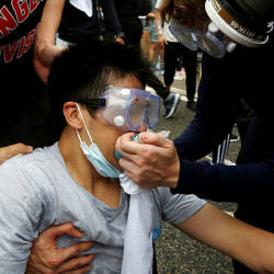 Protesters help a man during the demonstration where tear gas was fired, in Hong Kong, China June 12, 2019.