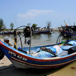 A fisherman pushes a boat into the sea today at Sungai Batu fisherman's jetty, one of the areas that will be affected by the Penang South Reclamation (PSR) project.