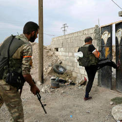 Turkey-backed Syrian fighters breakopen the front door of a house at a postition that they are holding in the Syrian border town of Ras al-Ain on Oct 19, 2019. — AFP