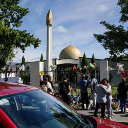 People gather outside the Al Noor Mosque after the main road that runs alongside it was opened to traffic in Christchurch on March 23, 2019. — AFP