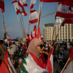 A demonstrator walks past Lebanese national flags during an anti-government protest in downtown Beirut, Lebanon October 22, 2019. — Reuters