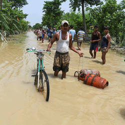 An Indian resident wades on a flooded road leading his bicycle and carrying gas bottles following heavy monsoon rains at Muzaffarpur district in the Indian state of Bihar today. — AFP