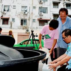 Kota Laksamana assemblyman Low Chee Leong (R), assists residents of an apartment in the area to store water from a tank, on Sept 15, 2019. — Bernama