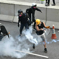 A protester (R, in yellow helmet) swings a tennis racquet to return a tear gas canister fired by riot police at Kowloon Bay in Hong Kong on Aug 24.