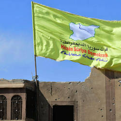 A picture taken on March 23, 2019 shows the US-backed Syrian Democratic Forces' (SDF) flag atop a building in the Islamic State group's last bastion in the eastern Syrian village of Baghuz after defeating the jihadist group. — AFP