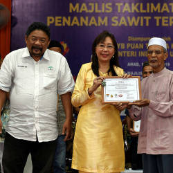 Primary Industries Minister Teresa Kok (2nd L) the Malaysian Sustainable Palm Oil (MSPO) certificate to, Sulong Muhamad, a smallholder in Terengganu, on Aug 18, 2019.