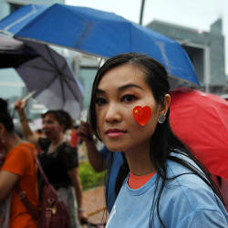 A pro-Beijing supporter displays a sticker with the China national flag on her face as she takes part in a pro-government rally at Tamar Park in Hong Kong on Aug 17.