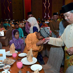 Home Minister Tan Sri Muhyiddin Yassin greets guests at the ministry's breaking fast event last night.