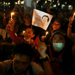 A placard mocking Thailand's Prime Minister Prayuth Chan-o-cha as Pinocchio is seen as activists hold up candles while gathering to demand quick elections to end military rule at a university in Bangkok, Thailand, Jan 19, 2019. — Reuters