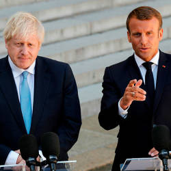 French President Emmanuel Macron (R) gestures as he delivers a speech to the press next to Britain's Prime Minister Boris Johnson (L) prior to their meeting at The Elysee Palace in Paris on Aug 22, 2019. — AFP