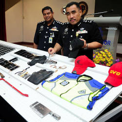 Selangor CID chief SAC Fadzil Ahmat (R) displays the material seized during the investigation of four people, who posed as police and immigration personnel during robberies, at a press conference at Selangor state contingent police headquarters, Shah Alam on April 19, 2019. — Bernama
