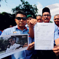 Major (retd) Md Razali Md Lani (C) and others present a police report lodged at the North Johor Baru District Police Headquarters today against two individuals who are alleged to have insulted the Malaysian Armed Forces. — Bernama