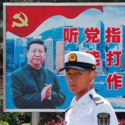 A People's Liberation Army Navy soldier stands in front of a backdrop featuring Chinese President Xi Jinping during an open day of Stonecutters Island naval base, in Hong Kong, China, June 30, 2019. - Reuters