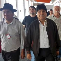 Handout photo released by the Argentina's Association of State Workers (ATE) and the Workers' Central Union of Argentina (CTA), of Bolivian ex-President Evo Morales (C) and Bolivian former Foreign Minister Diego Pary Rodriguez (L) walking upon their arrival at Ezeiza airport in Buenos Aires on Dec 12. — AFP