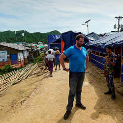 Officials of UN and Bangladesh police stand guard in front of a place where UN and refugee commission interviewed Rohingya families at a refugee camp in Teknaf on Aug 21.