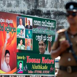 A policeman stands guard at a roadblock near an electoral poster of deputy leader of the ruling United National Party (UNP) and New Democratic Front presidential candidate Sajith Premadasa before a campaign rally in Colombo on November 13, 2019. - AFP