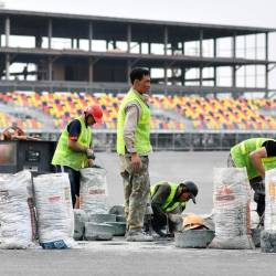 In this file photo taken on February 14, 2020, workers set up a kerb on the track at the under-construction Formula One Vietnam Grand Prix race track site in Hanoi, amid concerns of the Covid-19 coronavirus outbreak. - AFP