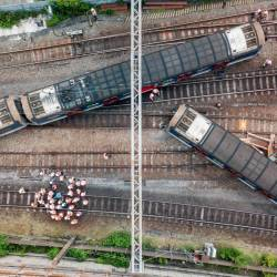 This aerial picture shows rescue workers standing on a railway track near a passenger train, after it derailed during rush hour outside Hung Hom station on the Kowloon side of Hong Kong on September 17, 2019. — AFP
