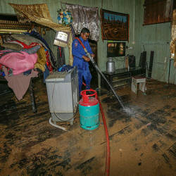 Civil Defence Department (JPA) personnel helps with the cleaning of a flood victim's home in Kampung Chuchuh Puteri A on Dec 4, 2019 —