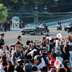 People cheer as the motorcade of Japan's Emperor Naruhito and Empress Masako leaves the Imperial Palace during a royal parade in Tokyo on November 10, 2019. - AFP
