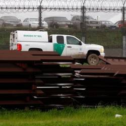 A US border patrol vehicle drives past metal sections to be used to fix the border fence between Mexico and the US, as seen from Tijuana, Mexico, on Feb 14, 2019. — Reuters