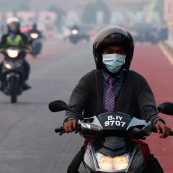 A man rides on a motorcycle in the haze in Putrajaya, Malaysia, September 17, 2019. - Reuters