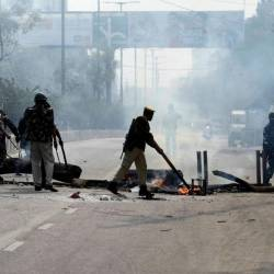 Police officers remove a burning blockade from a road in Guwahati on December 12, 2019. - AFP