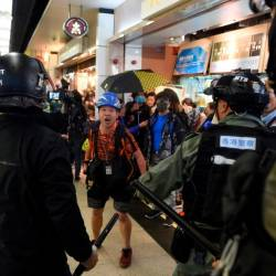 A photojournalist (C) argues with police during a protest at the New Town Plaza shopping mall in Shatin in Hong Kong on December 15, 2019. - AFP