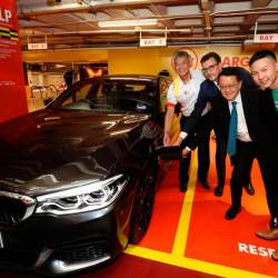 From left: Lo, Hoelzl, Cheah and Chan plugging a charging socket into the charging pod of a BMW 530e M Sport PHEV during the launch at Sunway Pyramid Convention Centre.
