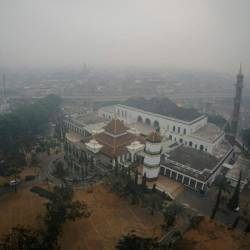 This aerial picture taken on September 20, 2019 shows haze covering the city of Palembang, South Sumatra. Indonesia is battling forest fires causing toxic haze across southeast Asia with aircraft, artificial rain and even prayer, President Joko Widodo said during a visit to a hard-hit area. — AFP