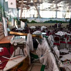 Afghan men investigate in a wedding hall after a deadly bomb blast in Kabul on August 18, 2019. — AFP