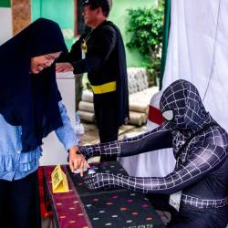 Indonesian election workers dressed in superhero costumes register voters at a polling station in Surabaya on April 17, 2019. — AFP