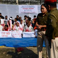 Police stand next to protestors taking part in a demonstration against the Indian government's Citizen Amendement Bill (CAB) in Guwahati on December 14, 2019. - AFP