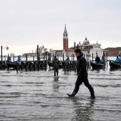 A man walks across the flooded Riva degli Schiavoni embankment with the San Giorgio Maggiore basilica in background, after an exceptional overnight Alta Acqua high tide water level, early on November 13, 2019 in Venice. - AFP