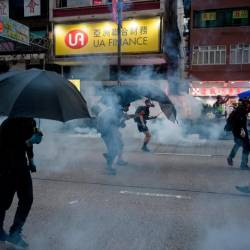 Protesters react to tear gas fired by police during a pro-democracy march along Nathan Road in the Kowloon district in Hong Kong on Oct 20, 2019. — AFP
