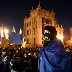 An activist wears Ukrainian flag attends a rally called Night Watch in front of President Volodymyr Zelensky office in Kiev, to demand no capitulation ahead of a summit in Paris, on Dec 8. — AFP